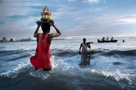 Devotee carries statue of Lord Ganesh into the waters of the Arabian Sea during the immersion ritual off Chowpatty beach, Mumbai, India, 1993, ultrachrome print, 40 x 60 inches/101.6 x 152.4 cm