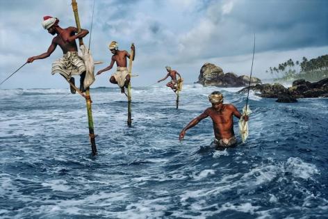 , Steve McCurry, Stilt fishermen, Weligama, South coast, Sri Lanka, 1995, ultrachrome print, 20 x 24 inches/50.8 x 60.96 cm; © Steve McCurry