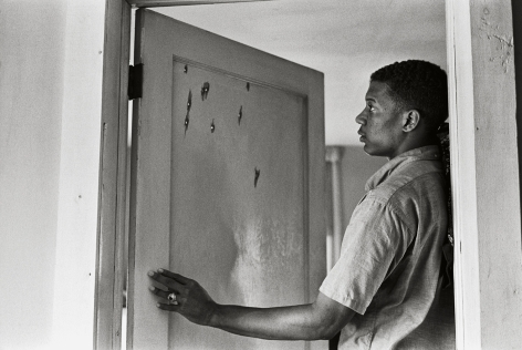 Jerome Smith Inspects Bullet Holes in Door, 1963, 16 x 20Inches, Silver Gelatin Photograph, Edition of 25