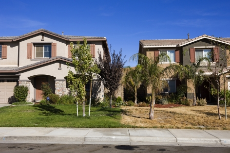 The property line between an abandoned home and its occupied neighbor in the Rosetta Canyon development, Lake Elsinore, California, 2008. Shared status in such master-planned communities collapsed when empty homes depressed the values of their neighbors' homes even further.