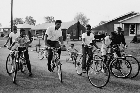 Muhammad Ali (Cassius Clay) Biking with Neighborhood Kids, Louisville, Kentucky, 1963, Silver Gelatin Photograph