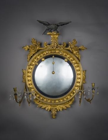 """""""Neo-Classical Convex Girandole Mirror with Candle Arms,"""" about 1810. American, probably Salem, Massachusetts. Eastern White Pine (Pinus strobus), gessoed and gilded, and partially ebonized, with convex mirror plate, glass drip pans, blown and cut, glass prisms, gilt-brass candle cups and bobeches, and brass chain 43 in. high, 38 in. wide, 10 5/8 in. deep"""
