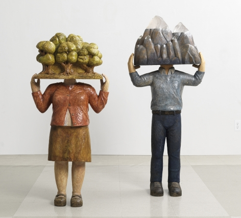 Sachiko Akiyama  On Finding Home, 2013  Wood, Paint, Gold Leaf  18 1/2h x 9 1/2w x 40d in. a sculpture featuring a figure with a mountain for a head accompanied by another statue of the same kind