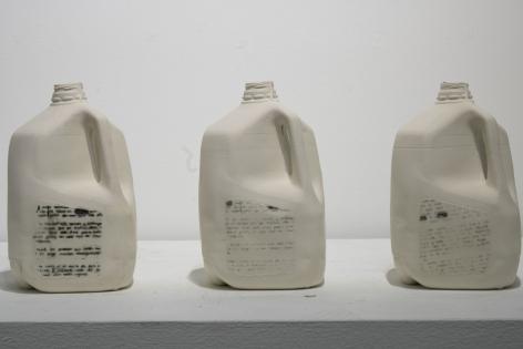 Cristina Colom-Munoz  Sueno Americano (American Dream), 2019  Slipcast Milk Jugs, screenprinted surface design  10 1/2h x 47 1/2w x 11 1/2d in 26.67h x 120.65w x 29.21d cm  CCM_001, sculptural installation of three gallon sized milk jugs with screen printed text