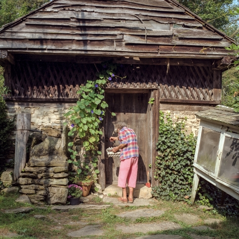 Ken Abbott, Ella Early, a beloved figure in Fairview, worked in the house for Annie Ager for many years. Here she is shown entering the spring house, behind the Big House, at Hickory Nut Gap Farm, 2005 Archival Pigment Print on Cotton Rag Paper, 15h x 15w in, Edition of 15, Photography