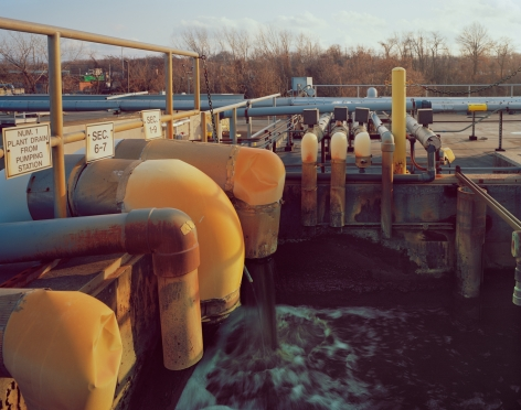 Influent, Sec. 6-7, 1-9, Photograph of a water treatment plant, water selling from orange pipes, grey and orange handrails, numerical signs
