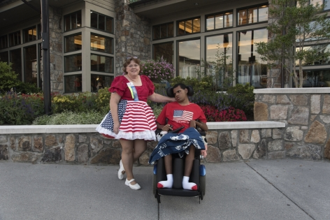 Stacy Kranitz  Gatlinburg, Tennessee, 2016  Archival Pigment Print  16 x 24 inches, Edition of 7  27 x 40 inches, Edition of 3, Woman in American Flag dress with man in a wheelchair, Tennessee