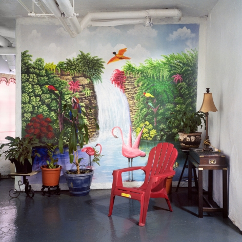 Untitled #51 (tropics), 2013  from the series Basement Sanctuaries  Archival pigment print  16 x 16 inches  Edition of 5, interior of a basement in NYC with a tropical wall mural of a waterfall, a red plastic chair and potted plants