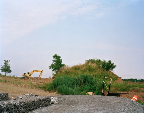 Old Landscape with New Interior Road and Gabion Wall, West Mound, 2019, Photograph of a mound of old landscaping, along a new road with big digger and other construction machinery in the distance, West Mound, Freshkills, NYC