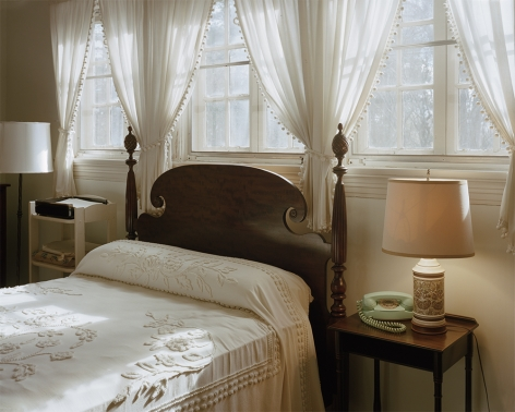 Tema Stauffer  Eudora Welty's Bedroom, Jackson, Mississippi, 2020  Archival Pigment Print  30h x 36w in. Eudora Welty's Bedroom showing bed in front of 3 windows with white sheer curtains, and end tables with lamp and green rotary phone