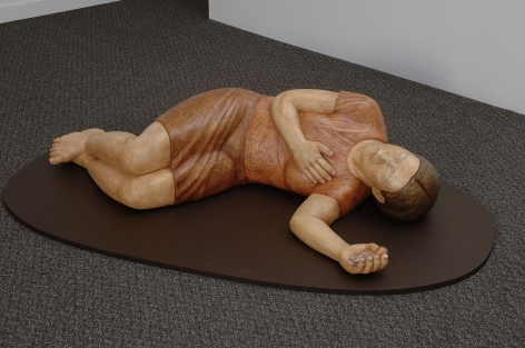 Sachiko Akiyama  I Remember What I Did Not See, 2010  Polychromed Wood  59h x 29w x 15d in. a wood sculpture of a figure lying on the ground in a restful position, with bird in left hand.