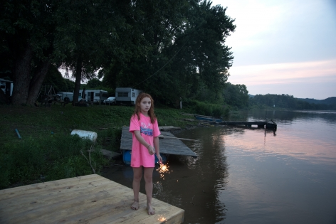 Letart, West Virginia, 2015  Archival Pigment Print  16 x 24 inches, Edition of 7  27 x 40 inches, Edition of 3, Young girl on dock with a spakler, West Virginia