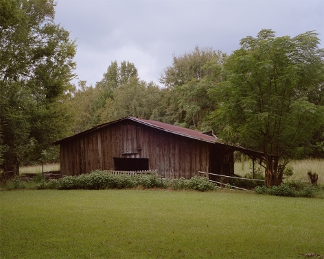 Tema Stauffer  Flannery O'Connor's Horse Barn, Andalusia Farm, Milledgeville, Georgia, 2018  Archival Pigment Print  30h x 36w in. a photograph featuring a barn for horses surrounded by trees with a grey cloudy sky
