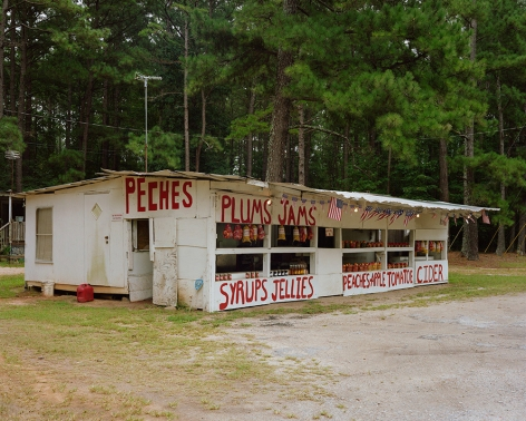 Tema Stauffer  Fruit Stand, Milledgeville Road, Georgia, 2018  Archival Pigment Print  30h x 36w in. a photograph featuring a fruit stand with various fruit names painted on the outer walls, on the side of the road in front of a wall of trees