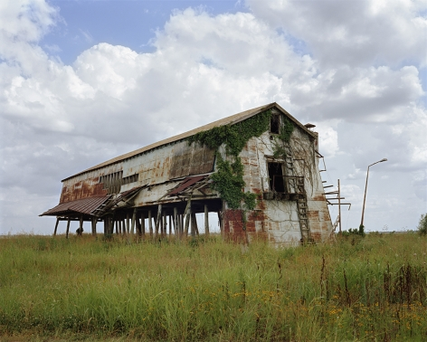 Tema Stauffer  Anderson Cotton Gin, Clarksdale, Mississippi, 2020  Archival Pigment Print  42h x 50 1/2w in. Andersons Cotton Gin Large Rusted steel structure on wooden stilts in a field of greenery with small yellow-orange flowers