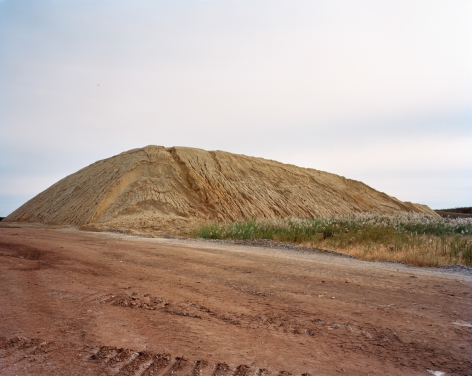 Photograph of a large sand pile, Freshkills, NYC. All neutral colors, rust and brown colors against a pale sky