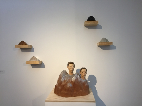 Sachiko Akiyama  Between Earth and Sky, 2012  wood, clay, paint,  17h x 17w x 17d in. a sculpture of two heads atop a range of mountains, with 4 smaller mountainous shapes mounted above
