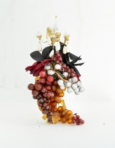 Botanicals, Grapes, 2020  Archival Pigment Print  50.8h x 40.64w cm  Edition of 5  30h x 24w in  76.2 h x 50.8w cm  Edition of 3, Still life with a bunch of real and plastic grapes of various colors (purple, red, white and golden) with silk leaves and chandelier earrings