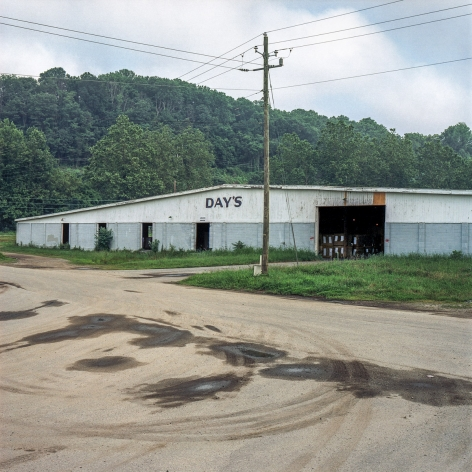 Ken Abbott  Day's Warehouse, Old Lyman St., Asheville, July 2003, Printed 2020  Archival Pigment Print  Images Size: 7 x 7 in Paper Size: 12 x 9 1/2 in Mat Size: 14 x 11 in  Edition of 10  $ 300.00 unframed, photograph of a long grey warehouse