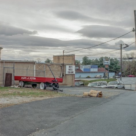 Ken Abbott  Radio Flyer and Pawn Shop, Patton Ave, November 2004, Printed 2020  Archival Pigment Print  Image Size: 7 x 7 in Paper Size: 12 x 9 1/2 in Mat Size: 14 x 11 in  Edition of 10  $ 300.00 unframed, photograph of a large red wagon in front of a grey warehouse