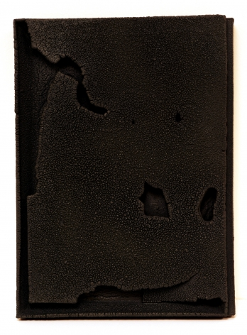 """Cary Esser, Parfleche (black), 2018, earthenware and glaze, 16"""" x 12"""" x 2"""", rectangular """"parfleche"""" made of eartheneware, fired to a rich black with various intentional voids in the surface a little like a moonscape"""