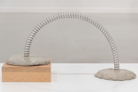 B. Wurtz sculpture of bent metal in cement with one side elevated on wood block