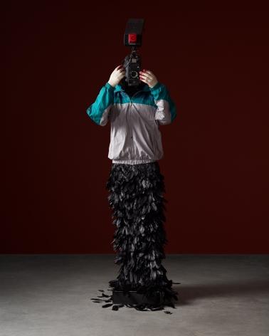 L'homme à la caméra, 2015 FRP mannequin, windbreaker, gloves, feathers, broadcast camera 88.58 x 26.77 x 22.83 inches 225 x 68 x 58 cm,
