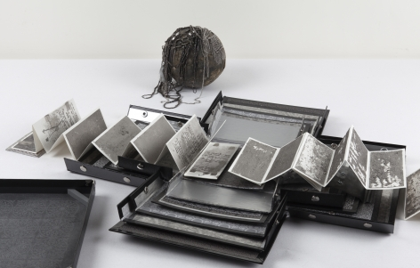 Silver, 2011 Aged silver metallic paper, paper, lead, necklaces, chain, bell, trinkets, oneleporellobook