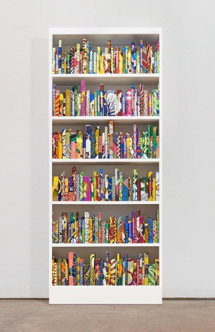 White wooden bookshelf containing approximately 225 hardback books bound in Dutch wax print cotton textile with names embossed in gold on their spines