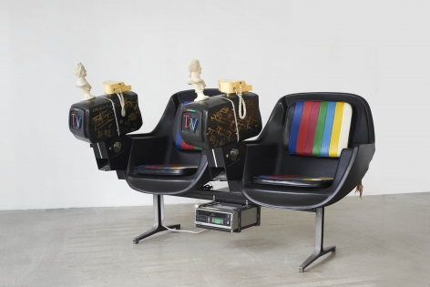 Two chairs attached to one another, each with their own small television monitor