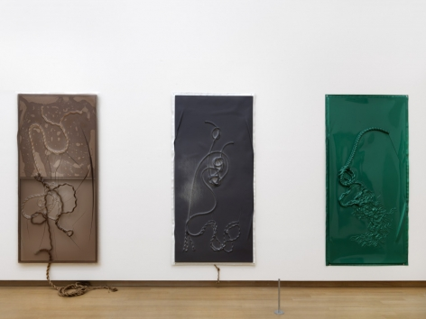 Three vacuum rope works that are vertically long. From left to right, the works are monochrome: brown, black, and dark green.