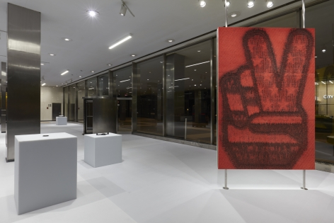 Various works of art by Adam McEwen presented at the Lever House Art Collection. The walls are ceiling to floor glass windows which show that it is night time.