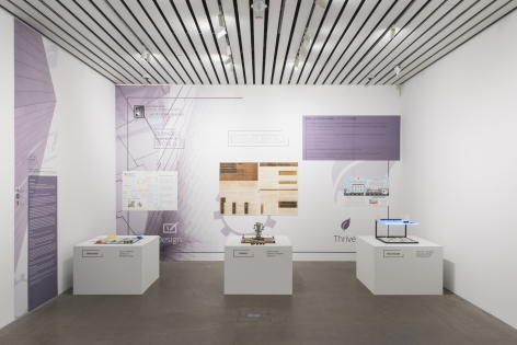 Installation image of The Founder's Paradox at the MCA Cleveland in 2018. there are several pedestals with works on them and textual vinyls on the wall behind them.