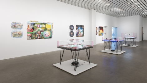 Installation of The Founder's Paradox at MCA Cleveland in 2018, featruing several tables with boardgames on them and covered in Plexi galss in the senter of the room and several large works on the wall that look like covers from board games.