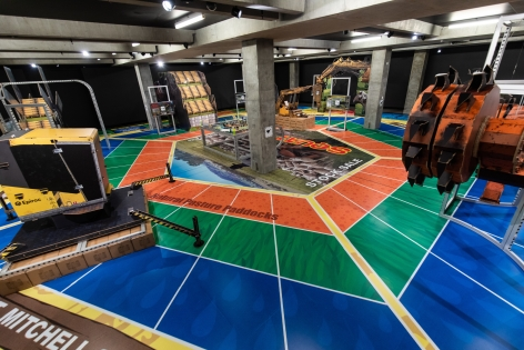 installation of MINE at MONA in 2020, featuring large vinyl on the floor that looks like a board game and several large cardboard sculptures of mining machinery standing on it.