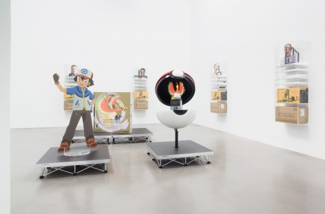 Installation of Blockchain future states at Petzel Gallery in 2016, featuring several dream boxes hanging on the walls and a large cut out of Ash from Pokemon on a pedestal with an open pokeball next to him.