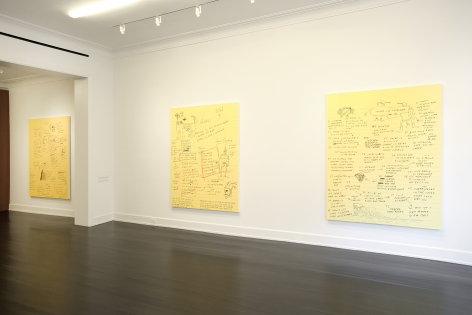 Three of the same sized paintings of text and doodles on yellow note paper are shown hanging side by side.