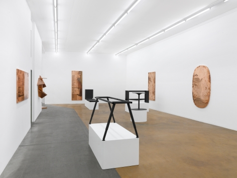 Installation view of Beshty's exhibition at MAMCO featuring several copper surrogates on the walls with table and desks without tops on pedestals in the center of the room.