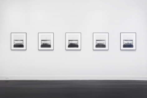 five framed laser exposed prints hanging on the white gallery wall. each print is of a glass case with shoes inside of them.