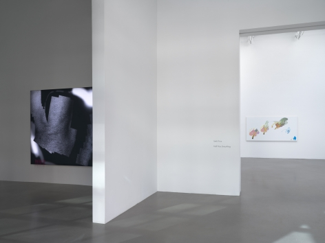A view of a black and white LED lit piece in a room in the forefront, and another more colorful work in a room farther in the distance.