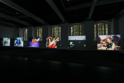 Six videos by price projected on side-by-side screens of the same size. The lights are off but the arched windows behind show the green silhouette of trees in the day time.