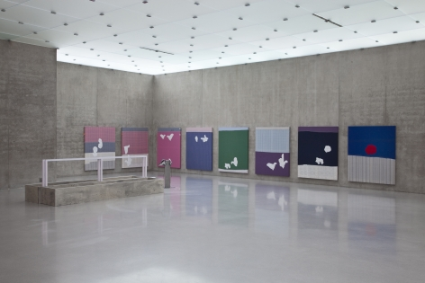 Installation view from Kunsthaus Bregenz in 2010. Eight textile paintings hang on two perpendicular walls. All are different colors and feature white gloved hands embroidered on them.