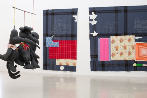 "Installation view of von Bonin's show at MUMOK featuring three large hanging stuffed birds, each wearing colorful scarves. Two patch-work cloth ""paintings"" hang in the background."