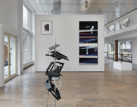 Installation view of Beshty's exhibition at Capitain Petzel featuring a deconstructed computer work in the center of the floor and a large black curl piece on the wall in the background.