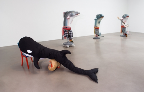 Installation image of a killer whale soft sculptures with three plastic mackrel sculptures in the background. Each mackrel is robed in gingham fabrics, one has a ukulele and another has a white electric guitar.