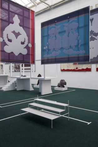 Installation view from documenta 12 featuring two of von Bonin's rorschach test fabric paintings. One is pink and purple with the white rorschach blob appliquéd on, and the second is light and dark blue with the white rorscah test appliquéd on. The paintings are hanging from the ceiling, below them are small white bleachers and in the background are white cubes on platforms and a large gray stuffec bulldog on a white platform.