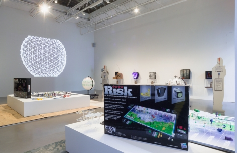 installation shot from Blockchain Futurue States at Petzel Gallery in 2016. features two risk game son pedestals and several case mods hanging on background wall.