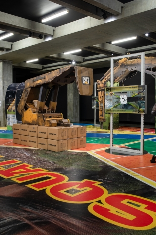 installation of MINE at MONA in 2020, featuring large vinyl on the floor that looks like a board game and a large cardboard sculpture of mining machinery standing on it.