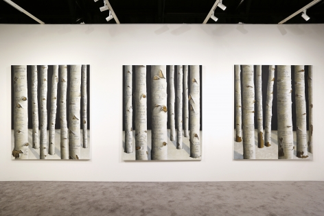 Three of the same sized paintings of a forest of trees with text scrawled into the bark is shown hanging side by side in an art fair booth.