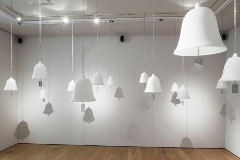 Marie Orensanz, ...in honor... of whom?, 1999-2015, 20 white opaline bells (9.5 x 10.2 in each) with stainless steel tags (3.1 x 1.8 in each), Installation view, 2015.